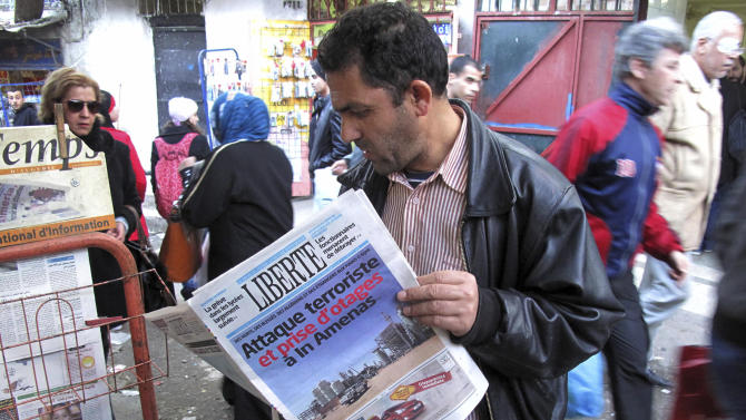 """A man reads a newspaper headlining """"Terrorist attack and kidnapping in In Amenas"""", at a news stand in Algiers, Thursday, Jan. 17, 2013. Algerian forces raided a remote Sahara gas plant on Thursday in an attempt to free dozens of foreign hostages held by militants with ties to Mali's rebel Islamists, diplomats and an Algerian security official said. Information on the Algerian assault in the remote area was wildly varying _ Islamic militants claimed that 35 hostages and 15 militants died in a strafing by Algerian helicopters, while Algeria's official news service claimed hundreds of local workers and half the foreigners were rescued. (AP Photo/Ouahab Hebbat)"""