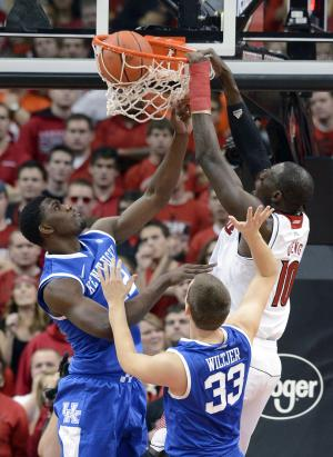 Louisville's Gorgui Dieng, right, dunks over Kentucky's Alex Poythrees, left, and Kyle Wiltjer during the first half of an NCAA college basketball game Saturday, Dec. 29, 2012, in Louisville, Ky. (AP Photo/Timothy D. Easley)