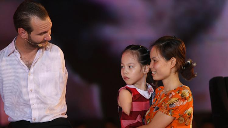 In this Thursday, May 23, 2013 photo, Serbian Australian evangelist Nick Vujicic, left, talks to Linh Chi, center, 8, who has no limbs, during his speech to a crowd of about 25,000 students and young people at My Dinh national stadium in Hanoi, Vietnam. Vujicic was born with tetra-amelia syndrome, a rare disorder characterized by the absence of all four limbs. Amid childhood bullying, he once tried to drown himself. (AP Photo/Na Son Nguyen)