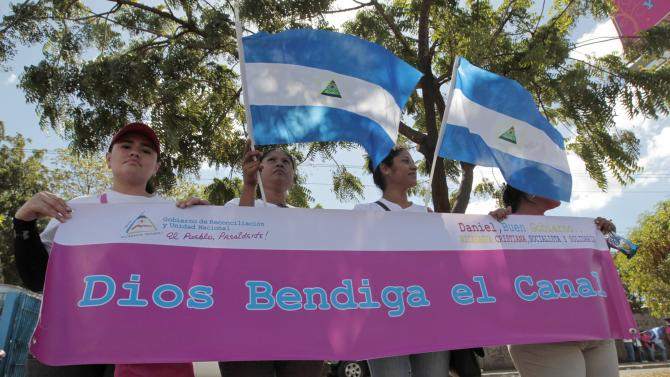 Supporters of Nicaragua's President Ortega hold a banner during the groundbreaking for the Interoceanic Grand Canal in Managua