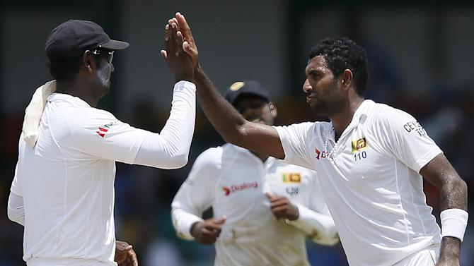 Sri Lanka's Prasad celebrates with captain Mathews after taking the wicket of India's Sharma during the fourth day of their third and final test cricket match in Colombo