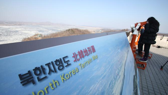 "A South Koreans girl looks at the North side through binoculars at a unification observation post in Paju near the demilitarized zone (DMZ) of Panmunjom, South Korea, Sunday, Jan. 27, 2013. Kim convened top security and foreign affairs officials and ordered them to take ""substantial and high-profile important state measures,"" state media said Sunday, indicating that he plans to push forward with a threat to explode a nuclear device in defiance of the United Nations. (AP Photo/Ahn Young-joon)"
