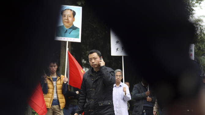 Communist loyalists stage a counter-protest with a portrait of former Chinese leader Mao Zedong against supporters of the Southern Weekly newspaper outside the newspaper's headquarters in Guangzhou in south China's Guangdong province Tuesday Jan. 8, 2013.  Free-speech protesters in masks squared off against flag-waving communist loyalists in a southern Chinese city Tuesday as a dispute over censorship at a newspaper spilled into the broader population, with authorities shutting  microblog accounts of supporters of the paper. (AP Photo) CHINA OUT