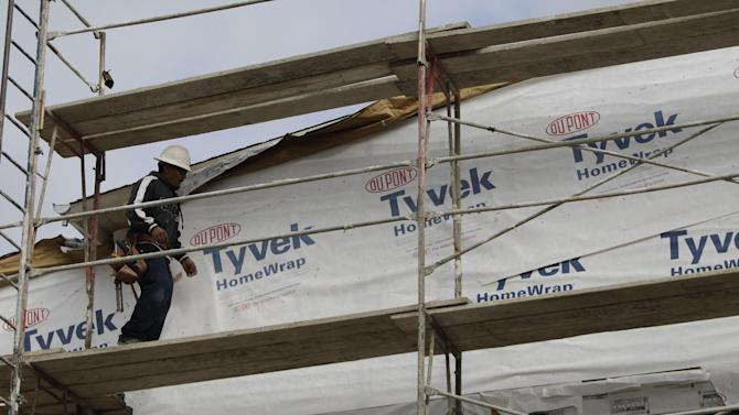 In this Feb. 16, 2011 photo, a construction worker uses Dupont Tyvek Home Wrap at a housing complex in Palo Alto, Calif. The DuPont Co. reported a 3 percent decline in second-quarter earnings Tuesday, July 24, 2012, as volumes were off in several business units and the company saw weakness in the market for a key product, titanium dioxide, particularly in Europe and Asia. (AP Photo/Paul Sakuma)