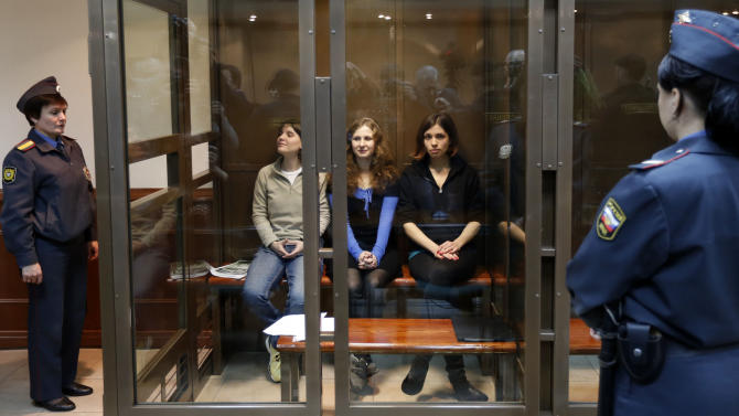 Feminist punk group Pussy Riot members, from left, Yekaterina Samutsevich, Maria Alekhina, and Nadezhda Tolokonnikova sit in a glass cage at a court room in Moscow, Wednesday. Oct. 10, 2012. Three members of the punk band Pussy Riot are set to make their case before a Russian appeals court that they should not be imprisoned for their irreverent protest against President Vladimir Putin. Their impromptu performance inside Moscow's main cathedral in February came shortly before Putin was elected to a third term. The three women were convicted in August of hooliganism motivated by religious hatred and sentenced to two years in prison. (AP Photo/Sergey Ponomarev)