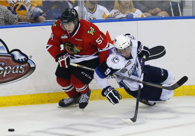 Saskatoon Blades' McColgan and Portland Winterhawks' Pouliot battle for the puck during the Memorial Cup Canadian Junior Hockey Championships in Saskatoon.