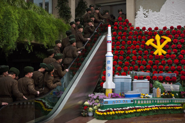 North Korean soldiers ride an escalator past a model of their country's Unha Rocket as they enter an exhibition in Pyongyang on Sunday, Feb. 17, 2013 where Kimjongilia flowers, named after the late No