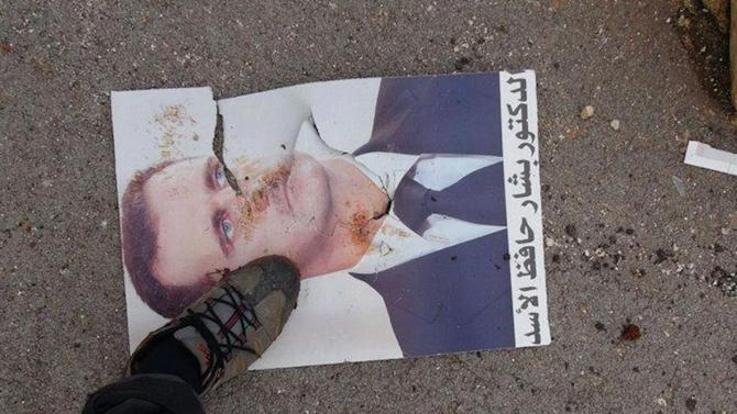 "This citizen journalism image provided by Edlib News Network, ENN, which has been authenticated based on its contents and other AP reporting, shows a Syrian rebel stepping on a portrait of Syrian President Bashar Assad, at Taftanaz air base that was captured by the rebels, in Idlib province, northern Syria, Friday Jan. 11, 2013. Islamic militants seeking to topple President Bashar Assad took full control of a strategic northwestern air base Friday in a significant blow to government forces, seizing helicopters, tanks and multiple rocket launchers, activists said. The Arabic words in the portrait read:""The doctor Bashar Hafez Assad"". (AP Photo/Edlib News Network ENN)"