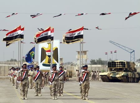 Iraqi Army soldiers march as part of a parade marking the founding anniversary of the army's artillery section in Baghdad