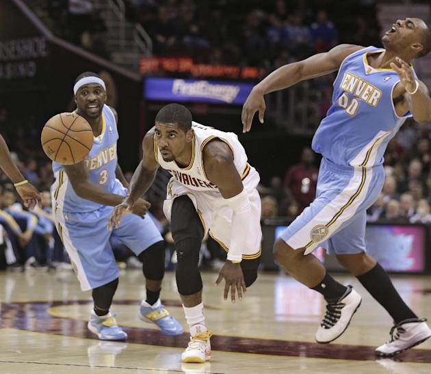 Cleveland Cavaliers' Kyrie Irving, center, gets between Denver Nuggets' Ty Lawson (3) and Darrell Arthur (00) during the first quarter of an NBA basketball game on Wednesday, Dec. 4, 2013, in