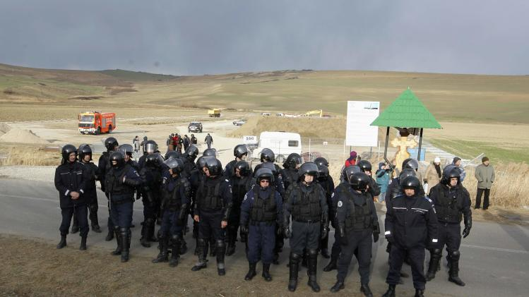 Gendarmes stand in front of a site of U.S. oil major Chevron during a protest by villagers and environmental activists against exploration for shale gas, in Pungesti