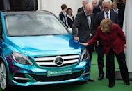 German Chancellor Angela Merkel (R) looks at a Mercedes E-drive electric car during the Electric Mobility conference on May 27, 2013. Germany plans to have one million electric vehicles on its roads by 2020, but so far that goal seems remote