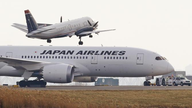 As a commuter plane lifts off, a Japan Airlines 787 is towed away from the runways at Logan Airport in Boston, Tuesday, Jan. 8, 2013. Officials say crews have contained a fuel leak from the outbound Japan Airlines flight to Tokyo in the second incident involving the airline at Logan in two days. (AP Photo/Charles Krupa)
