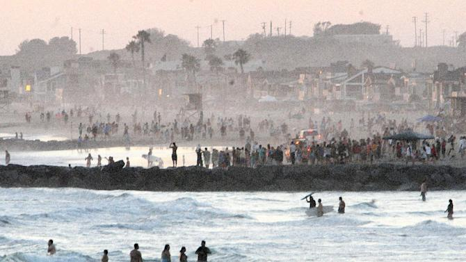 In this Sunday, July 6, 2014 photo, beachgoers watch as Newport Beach Lifeguard boats, and lifeguards search for a missing lifeguard in the late afternoon on Sunday, July 6, 2014. Ben Carlson, 32, a Newport Beach lifeguard who drowned while trying to rescue a swimmer, was finally pulled from the water by fellow lifeguards following a frantic, three-hour search. (AP Photo/Richard Koehler)