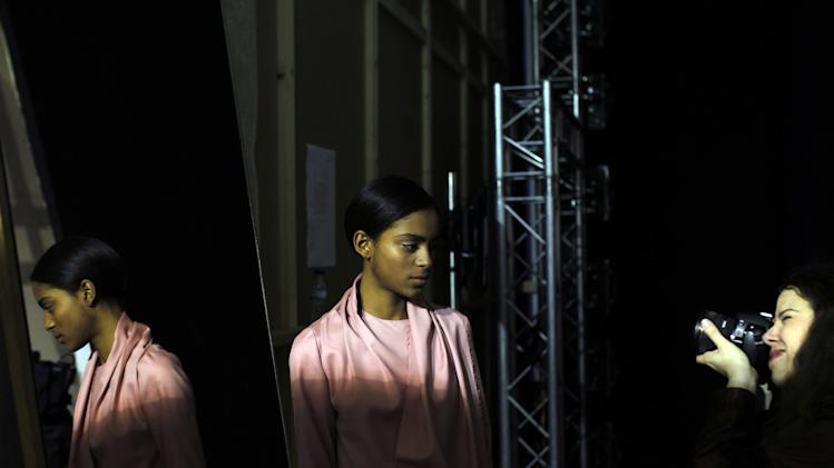 A model poses for a photographer backstage before a show during the ModaLisboa fashion week, in Lisbon, Portugal Sunday, March 9, 2014. (AP Photo/Francisco Seco)