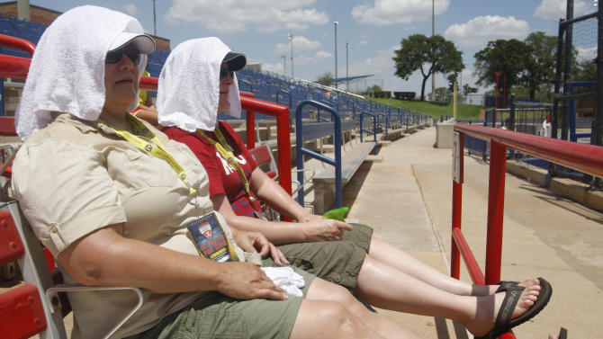 FILE - In this July 21, 2011 file photo, Liz Moody, left, and Stephanie Russell, right, both of Forest Grove, Ore., cover their heads with towels to keep cool as they watch the Japan-Canada World Cup of Softball game in Oklahoma City. After recalculating data from 2011, the nation's climatologists are declaring that Oklahoma suffered through the hottest summer ever recorded in the U.S. last year — not Texas as initially announced last fall. (AP Photo/Sue Ogrocki, File)