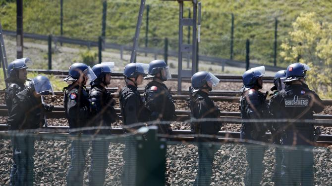 French gendarmes stand near the tracks after workers operating on the MyFerryLink car and passenger ferry boats set tires into fire at the entrance of the Eurotunnel Channel Tunnel linking Britain and France in Coquelles near Calais