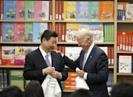 Chinese Vice President Xi Jinping and Vice President Joe Biden hold t-shirts given to them by students at the International Studies Learning Center in South Gate, Calif. , Friday, Feb. 17, 2012. (AP Photo/Damian Dovarganes)