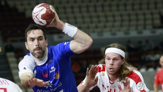 Hallgrimsson of Iceland is challenged by Hansen of Denmark during their round of 16 match of the 24th men's handball World Championship in Doha