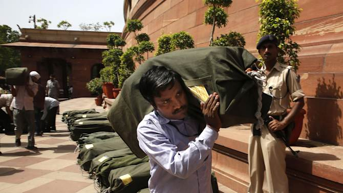 An Indian worker carries a sack containing copies of the 2014-15 union budget at the Indian parliament in New Delhi, Thursday, July 10, 2014. India's new government has introduced an ambitious reform-minded budget focusing on promoting manufacturing and infrastructure, raising the tax base and overhauling populist subsidies. (AP Photo/Manish Swarup)