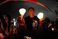 People take part in a candlelight vigil in Hong Kong. Hong Kong held a candlelight vigil Monday to mark the 23rd anniversary of the Tiananmen Square crackdown, in stark contrast to mainland China where activists said hundreds of people were detained