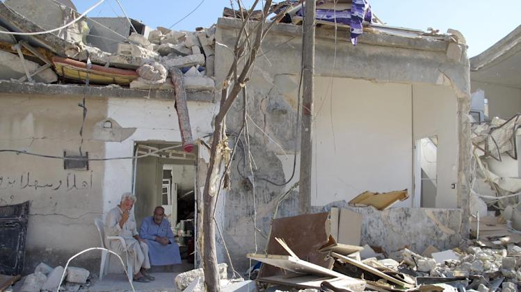 Syrians Bassem Kharfani, left, and Mahmoud Jikar sit at the door of Jikar's house, one of more than a dozen homes destroyed in a Syrian government bombing last week that killed more than 40 people, in Azaz, Syria, Monday, Aug. 20, 2012. (AP Photo/Ben Hubbard)
