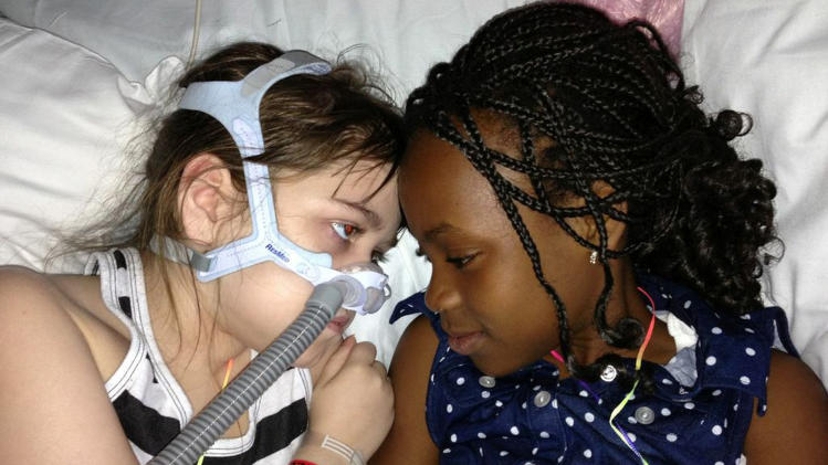 FILE - In this May 30, 2013 file photo provided by the Murnaghan family, Sarah Murnaghan, left, lies in her hospital bed next to adopted sister Ella on the 100th day of her stay in Children's Hospital of Philadelphia. Murnaghen, whose efforts to qualify for an organ donation drew public debate over how donated lungs are allocated was getting a transplant Wednesday, June 12, 2013, at Children's Hospital of Philadelphia, her family said. (AP Photo/Murnaghan Family, File)