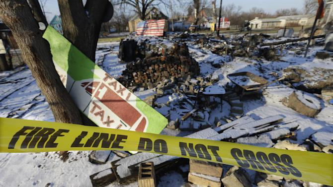 In a photo from Tuesday, Dec. 10, 2013 at the Heidelberg Project in Detroit, fire tape is seen surrounding the aftermath of the fire at the House of Soul. There have been at least eight fires since early May leading to questions about who might be targeting the installation and why they want to burn it down. Founder and artistic director Tyree Guyton and his compatriots vow to carry on, make more art and overcome the assault on his vision, yet worry threatens the whimsy as the fires snuff out building after building. (AP Photo/Carlos Osorio)