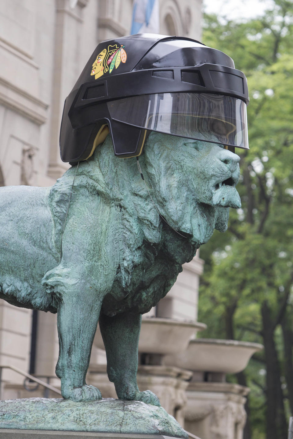 An oversized Chicago Blackhawks hockey helmet sits on one of the lion sculptures outside the entrance to the Art Institute of Chicago in celebration of the team's upcoming appearance in the Stanley Cup finals Wednesday, June 12, 2013, in Chicago. The Blackhawks host the Boston Bruins in Game 1 on Wednesday. (AP Photo/Scott Eisen)