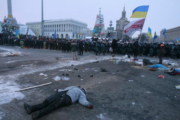 A pro-European protester lies on the ground near riot police occupying Independence Square in Kiev