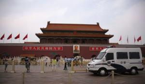 A police car guards in front of a giant portrait of China's late Chairman Mao Zedong at Tiananmen Square in Beijing