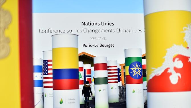 A woman walks past pillars with the  national flags of countries attending the COP 21 UN climate conference, in Le Bourget, north of Paris