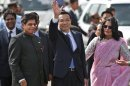 Chinese Premiere Li Keqiang waves as he is received by Indian Junior Minister for External Affairs, E. Ahamed, left, after he arrives in New Delhi, India, Sunday, May 19, 2013. Just weeks after a tense border standoff, China&#039;s new premier arrived in India on Sunday for his first foreign trip as the neighboring giants look to speed up efforts to settle a decades-old boundary dispute and boost economic ties. A woman at right is a protocol officer. (AP Photo/ Saurabh Das)