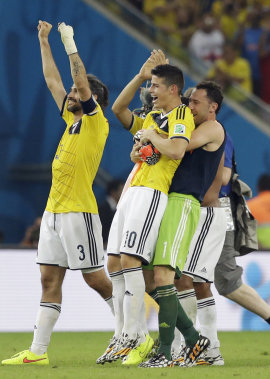 James Rodriguez (10) is lifted off his feat by his teammates following Colombia's 2-0 victory over Uruguay.  (AP)