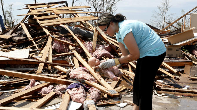 LaTisha Garcia finds a doll belonging to one of her daughters as she searches through the rubble of her tornado demolished home following Monday's tornado in Moore, Okla., Thursday, May 23, 2013. (AP Photo/Sue Ogrocki)