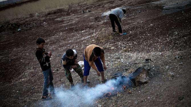 Syrian displaced children make a fire in a refugee camp near Azaz, Syria, Tuesday, Oct. 23, 2012. (AP Photo/ Manu Brabo)