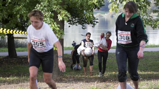 """Women carry bags with sand as they take part in a """"Brave Run"""" competition in Minsk"""