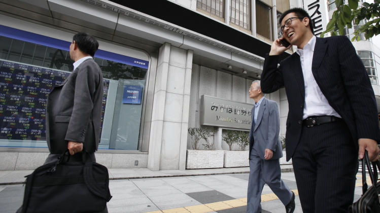 People walk past a digital display of Tokyo stock prices at a securities firm in Tokyo Monday, July 2, 2012. Asian stock markets inched higher Monday amid continued optimism over Europe's moves to ease its debt crisis and economic malaise. (AP Photo/Koji Sasahara)