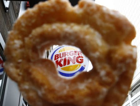 The Burger King logo is seen through a Tim Horton's doughnut hole in a photo illustration outside a restaurant in Toronto