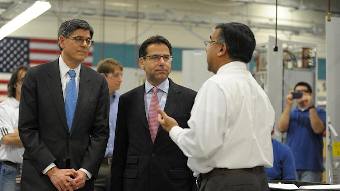 An employee takes pictures as Treasury Secretary Jacob Lew, left, tours the Siemens manufacturing plant with Siemens CEO Helmuth Ludwig and plant manager Shujath Ali, right, where electrical drive components for heavy machinery are assembled in Alpharetta, Ga., Thursday, March 14, 2013. The drive technology facility produces drive trains for customers including AMTRAK, Caterpillar and the new Atlanta Streetcar initiative. (AP Photo/David Tulis)