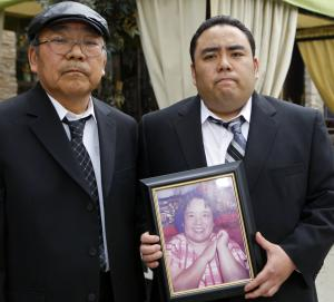 "FILE - This Thursday, Feb. 4, 2010 file photo shows Jeffrey Uno, right, and his father, Peter Uno, the son and husband of Noriko Uno, seen in framed photo, who died in an alleged ""sudden unintended acceleration"" crash in a Toyota Camry in August 2009, after a news conference in Los Angeles. Noriko Uno's case, in which her family claims her vehicle accelerated suddenly despite her efforts, is the first headed to trial, where the Japanese automaker is accused of covering up defects that led to her death. (AP Photo/Damian Dovarganes, File)"