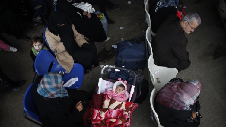 Palestinian girl sleeps next to her mother as they wait to cross into Egypt, at Rafah crossing between Egypt and the southern Gaza Strip