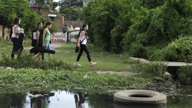 "In this Dec. 11, 2012 photo, young women carry their instruments as they walk alongside a polluted stream to their music practice session with ""The Orchestra of Instruments Recycled From Cateura"" in Cateura, a vast landfill outside Paraguay's capital of Asuncion, Paraguay. The community of Cateura could not be more marginalized. But the music coming from garbage has some families believing in a different future for their children. (AP Photo Jorge Saenz)"