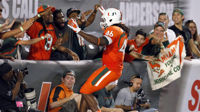 Miami tight end Clive Walford (46) celebrates with fans after scoring a touchdown during the second half of an NCCA college football game against South Florida, Saturday, Nov. 17, 2012 in Miami. Miami defeated South Florida 40-9. (AP Photo/Wilfredo Lee)