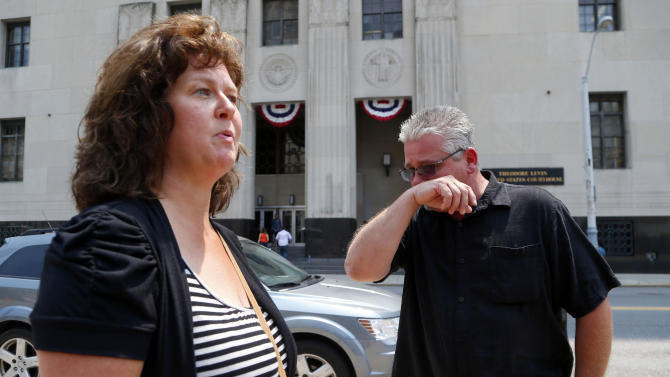 """Terry Spurlock, right, of Holly, Mich., a former patient of Dr. Farid Fata, speaks with his wife Nikii outside federal court, Monday, July 6, 2015, in Detroit. Patients of Fata received """"stunning"""" doses of a powerful, expensive drug that exposed them to life-threatening infections, an expert testified Monday as a judge heard details about a cancer specialist who fleeced insurance companies and harmed hundreds of people. (AP Photo/Paul Sancya)"""