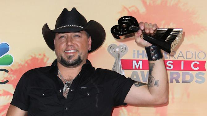 "Jason Aldean poses in the press room with the award for country song of the year for ""Burnin' It Down"" at the iHeartRadio Music Awards at The Shrine Auditorium on Sunday, March 29, 2015, in Los Angeles. (Photo by John Salangsang/Invision/AP)"