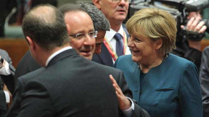 Bulgarian President Rosen Plevneliev, background third left, talks with German Chancellor Angela Merkel, right, as French President Francois Hollande, second left, talks to Malta's Prime Minister Joseph Muscat at an EU summit in Brussels on Wednesday, May 22, 2013. Leaders from the 27 European Union countries gather in Brussels for one of their regular European Council sessions. On the agenda is the increasingly controversial subject of tax evasion. (AP Photo/Yves Logghe)
