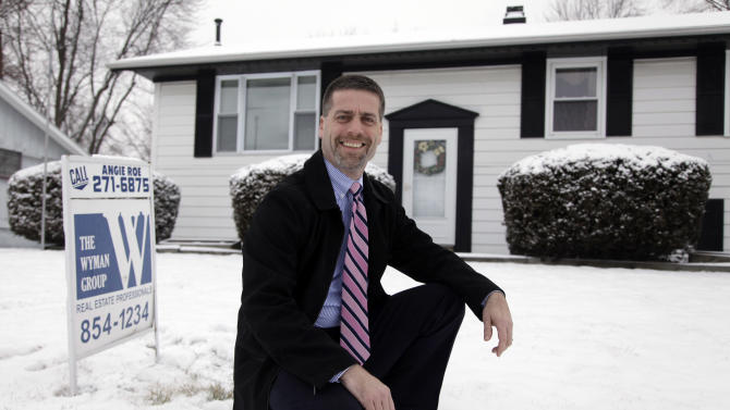 In this Feb. 14, 2012 photo, Paul Wyman, a realtor and Republican County Commissioner, poses outside a foreclosed home for sale in Kokomo, Ind. In 2009, 40 percent of home sales in Kokomo were foreclosures, says Wyman. At its worst, in the first quarter of that year, average home sale plummeted to about $30,000, compared with $110,000 in the previous two years. The U.S. auto industry has staged an amazing comeback, and the town's largest employer, Chrysler, has pledged to invest nearly $1.3 billion into its plants here, added about 1,000 workers and helped boost Kokomo's fortunes - it was honored in 2011 by the state chamber as Community of the Year. (AP Photo/Michael Conroy)