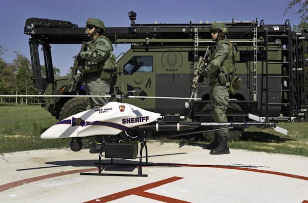 This Sept. 2011 photo provided by Vanguard Defense Industries, shows a ShadowHawk drone with Montgomery County, Texas, SWAT team members. A third of Americans worry their privacy will suffer if drones like those used against U.S. enemies overseas become the latest police tool for tracking suspected criminals at home, according to an Associated Press-National Constitution Center poll. Congress has directed the Federal Aviation Administration to come up with safety regulations that will clear the way for routine domestic use of unmanned aircraft within the next three years. (AP Photo/Lance Bertolino, Vanguard Defense Industries)