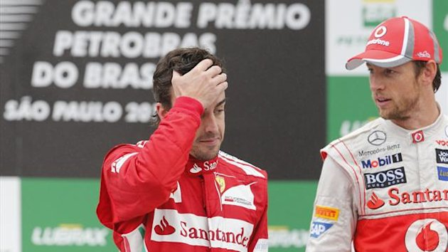 Second placed Ferrari Formula One driver Fernando Alonso of Spain (L) gestures next to race winner McLaren driver Jenson Button of Britain on the podium after the Brazilian F1 Grand Prix at Interlagos  (Reuters)